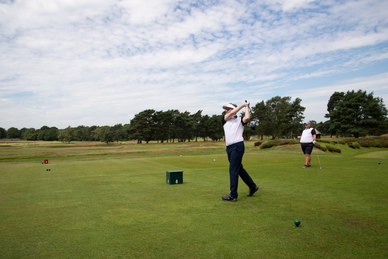 人站在草地上打高尔夫球  描述已自动生成